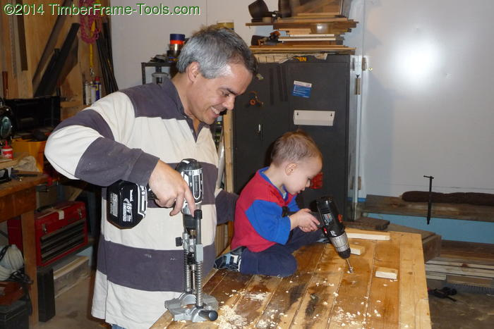 Child drilling with dad.